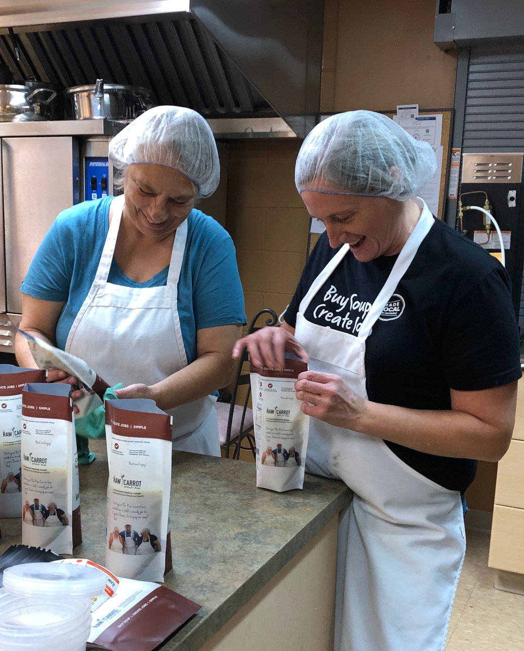two smiling employees packaging soup.